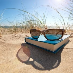 35905322 - book and sunglasses on the beach for summer reading and relaxing