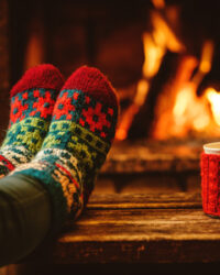 46927059 - feet in woollen socks by the christmas fireplace. woman relaxes by warm fire with a cup of hot drink and warming up her feet in woollen socks. close up on feet. winter and christmas holidays concept.